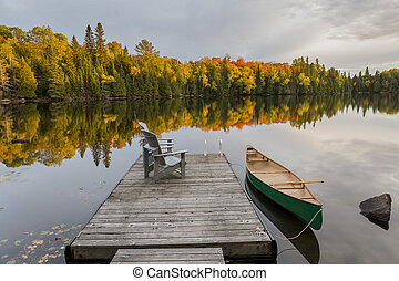 Canoe tied to a dock on an autumn lake in Ontario, Canada