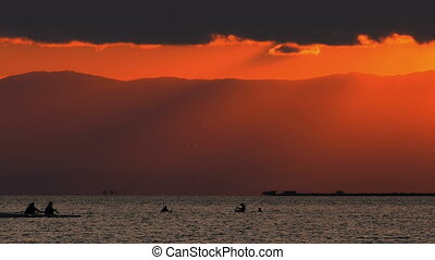 Canoe and Mussel Fishing People Silhouette in Sea and Sunset