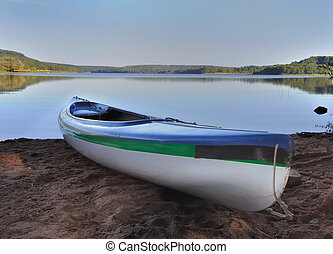 canoe at the edge of a lake