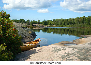 Cedar strip canoe sitting in water next to rocky shoreline