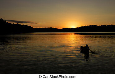Canoe - canoe on lake with sunset in silhouette