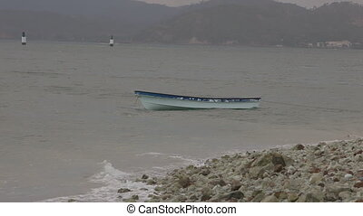Canoe Floats in Rough Water - Steady, medium wide shot of a...