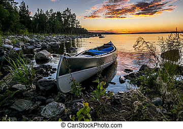 Canoe is at the shore of the lake