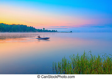 Canoe on a forest lake at sunrise