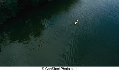 Canoe on a river, aerial view - Person paddling on canoe on ...