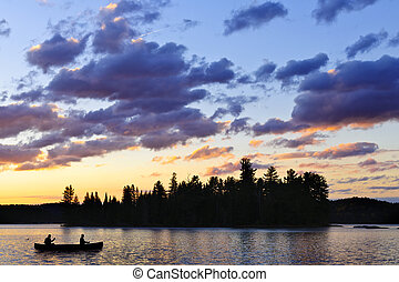 Canoe on lake at sunset - Silhouette of island and canoe on ...