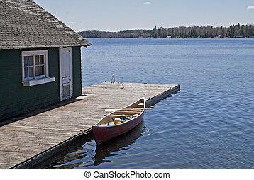 Canoe on lake docked by boat house