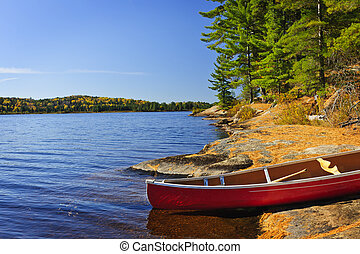 Canoe on shore - Red canoe on rocky shore of Lake of Two...