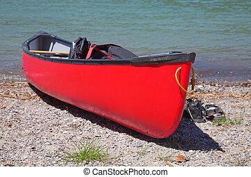 Canoe on the stone beach of swiss mountain lake