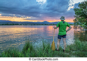 canoe paddler watching sunset