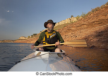 canoe paddling in Colorado - mature adult paddler in an ...