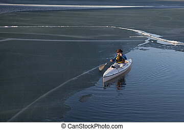 canoe paddling on ice covered lake