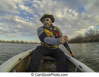 canoe paddling - senior male paddling a canoe on calm lake ...