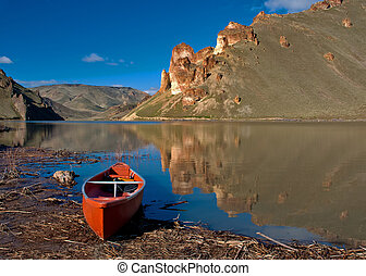 Canoe rests on the shore of a lake