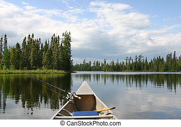 Canoe with fishing gear heading out on northern lake -...