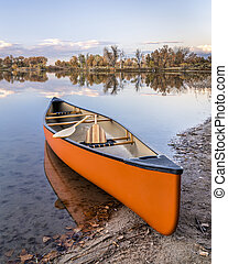 canoe with paddles on a lake shore