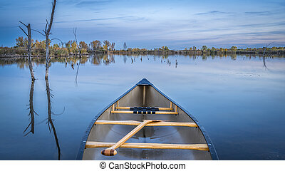 canoe with wooden paddle on a lake
