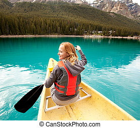 Canoe Woman Detail - A happy woman in a canoe on a clear...