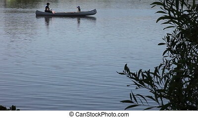 canoeing - a father and son in a canoe on a lake with copy...