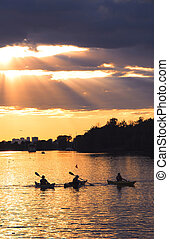 Canoeing - Group of people canoeing at sunset with sunrays...