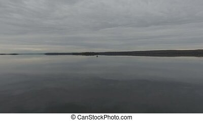 Canoeing on a calm lake - aerial approach of two girls...