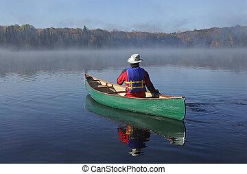 Canoeing on an Autumn Lake - Canoeist Paddling a Green Canoe...