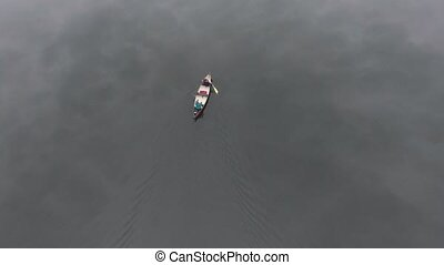 Canoeing on dead calm water - Aerial shot of a canoe with...