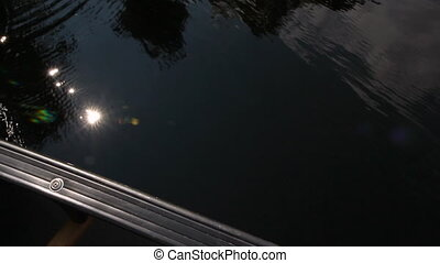 Canoeing. - POV shot of man in canoe. Reflection of sun, sky...