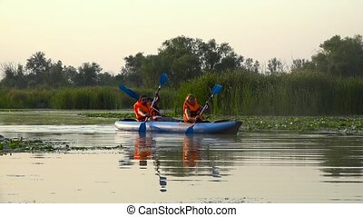 Canoeists paddle along the river. Slow motion - Tourists...