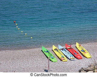 A line of brightly coloured canoes on a beach