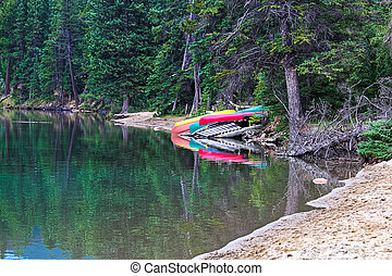 Canoes lined up on a dock along a lake