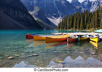 Morning light on colorful canoes along the shore of Moraine Lake, Banff National Park, Alberta, Canada.