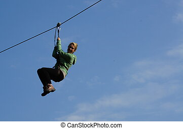 Canopy Adventure - Girl on a zip wire in a tree canopy