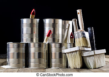 Cans of paint and brush on a wooden table. Painting with...