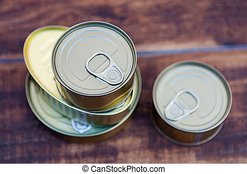 Cans of preserves on an aged wooden background