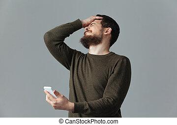 cansado, homem, segurando, smartphone