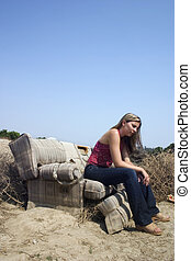 Trashy - A young woman sitting in an old, beat up, dirty...
