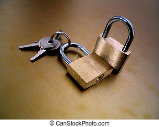 Lock and Keys - Two padlocks and a set of keys on a gold...