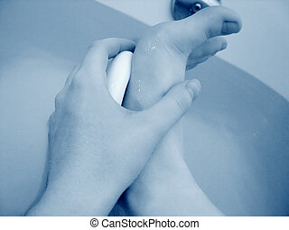 Cleaning Feet - Hand holding white soap, cleaning bottom of...