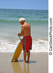 Board Time - A man preparing to hit the waves with his...