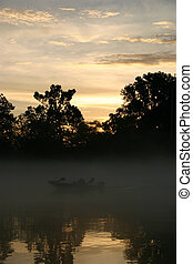 Misty sunset - A photo of a fishing boat manouvering on mist...