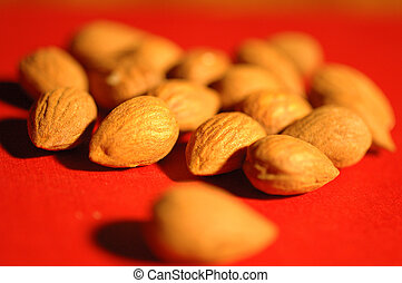 nuts - close-up of salted nuts on red background