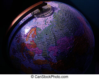 Global View - A globe with light cast on its surface, dark...