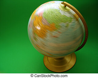 Spinning Globe - A globe being spun on its axis on a green...