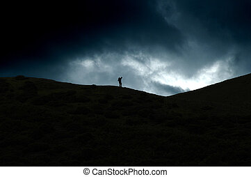 hill walker - silhouette of a man walking the long mynd,...