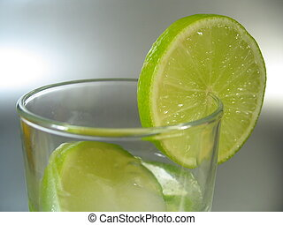 Glass with Lime - A glass with lime slices.