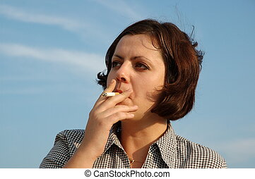 smoking girl - a pretty young girl smoking cigaret against...