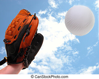 Fly Ball - Girl's hand in softball glove ready to catch a...