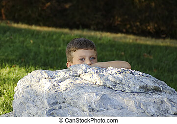 Peek-A-Boo - Photo of Toddler Behind a Large Rock.