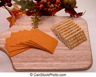 Cheese and Crackers - A wooden tray of cheddar cheese and...